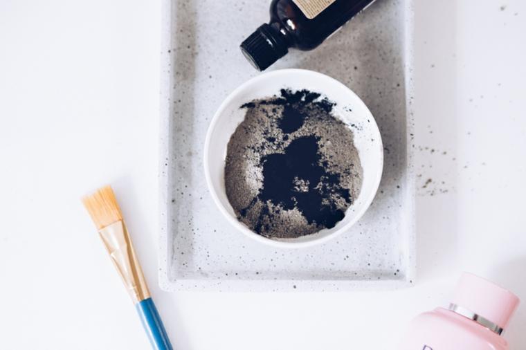 Maschera viso idratante fai da te, piattino con polvere di argilla e gocce di olio essenziale