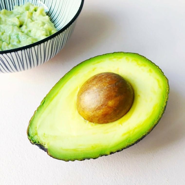 Un avocado tagliato a metà, maschera purificante fai da te, piatto con avocado frullato