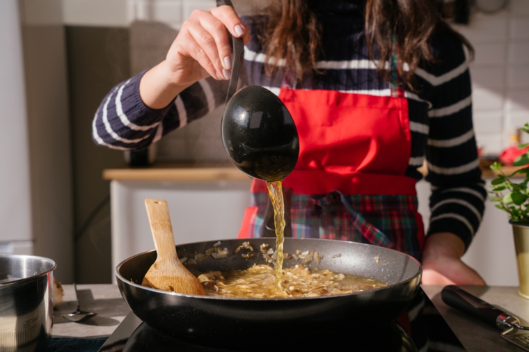 Donna che versa il brodo su una padella, ricette estive primi piatti