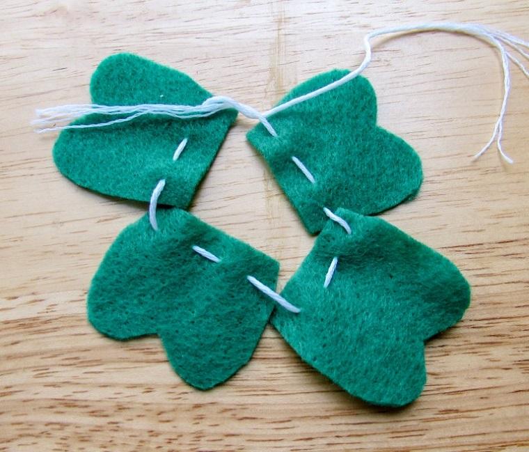Legare un filo di colore bianco, pezzettini di feltro di colore verde, creare segnalibri