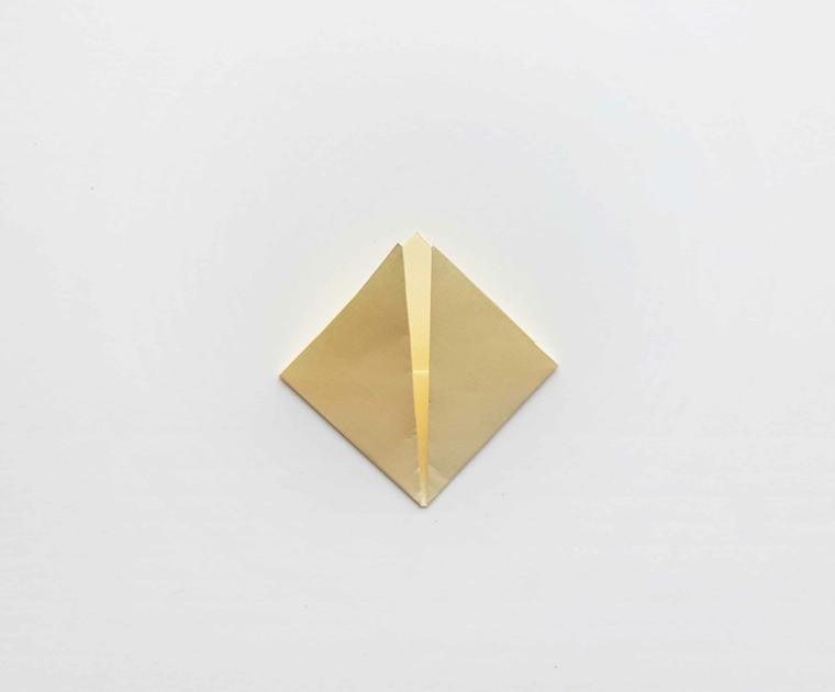 Origami con un foglio di colore bianco crema piegato, segnalibri fatti a mano