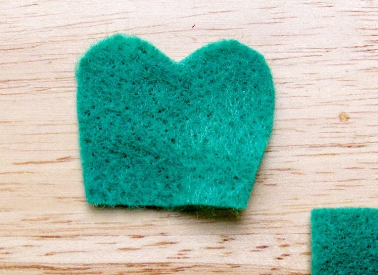 Pezzo di feltro verde a forma di cuore, un cuore di feltro sul tavolo, segnalibri fatti a mano