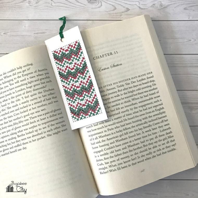 Segnalibro con cuciture, libro su un tavolo di legno, segnalibro con filo di lana
