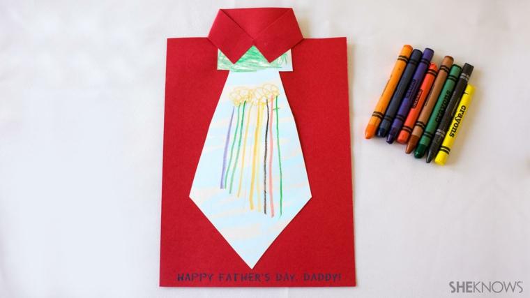 Cartolina di foglio rosso con cravatta colorata, pastelli colorati accanto ad una cartolina