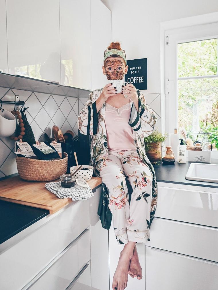 Donna seduta sul piano della cucina con tazza in mano, maschera viso idratante fai da te