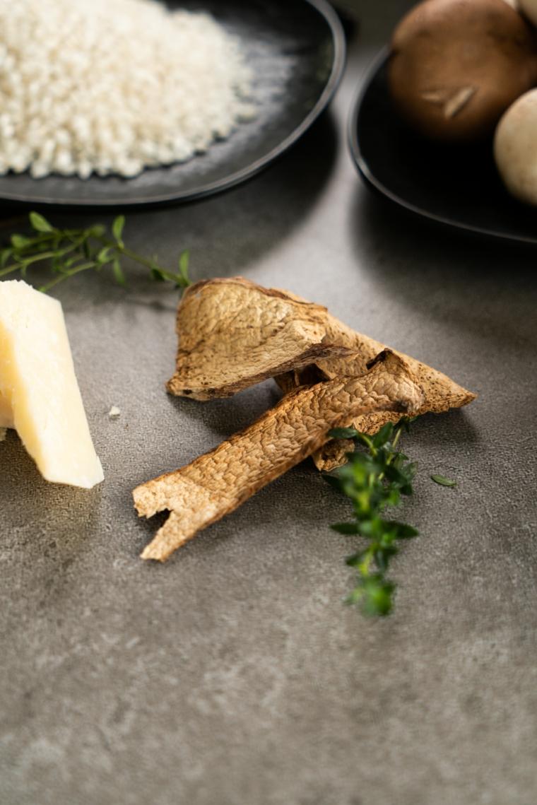 Cena veloce e appetitosa. ingredienti in piatti su un tavolo da cucina, pezzettino di formaggio e funghi secchi