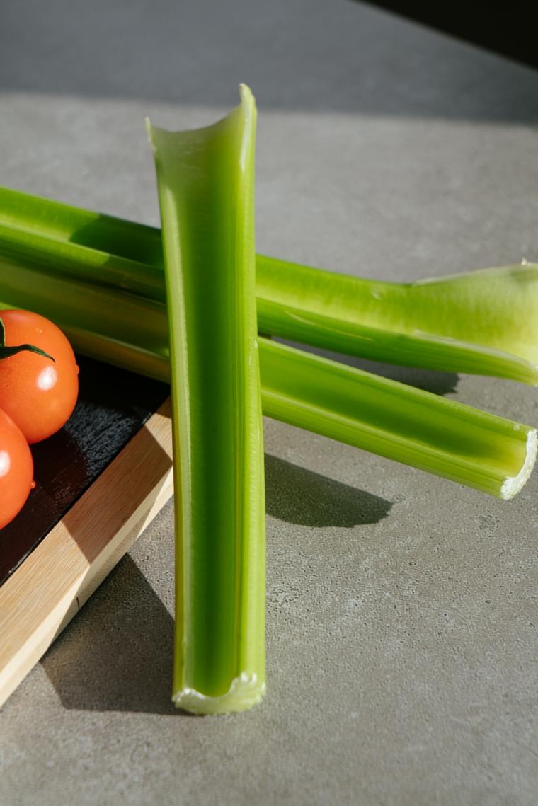Gambo di sedano e pomodori, ricette primi piatti veloci, mestolo di legno sotto le verdure