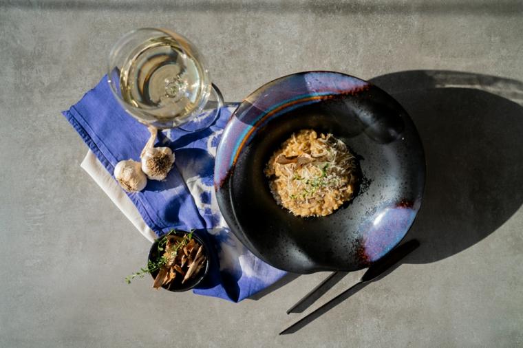 Piatto con risotto ai funghi, primi piatti veloci ed economici, bicchiere di vino bianco