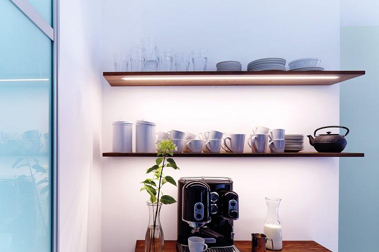 Mensole della cucina con tazze e piattini, illuminazione sotto le mensole