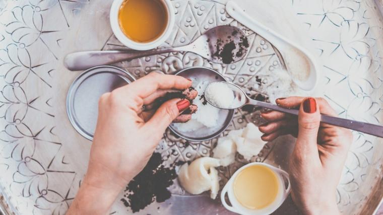 Maschera viso fai da te, polvere di caffè e zucchero, tazzina con del miele