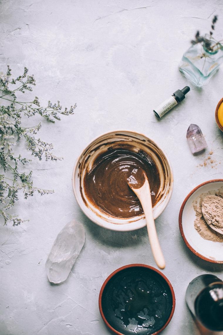 Ciotola con impasto di colore marrone, bottiglietta con olio essenziale