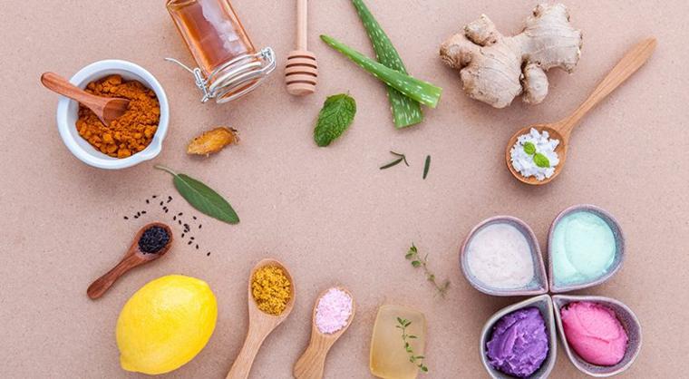Ingredienti posizionati su un tavolo, ciotola con curcuma, radice di zenzero