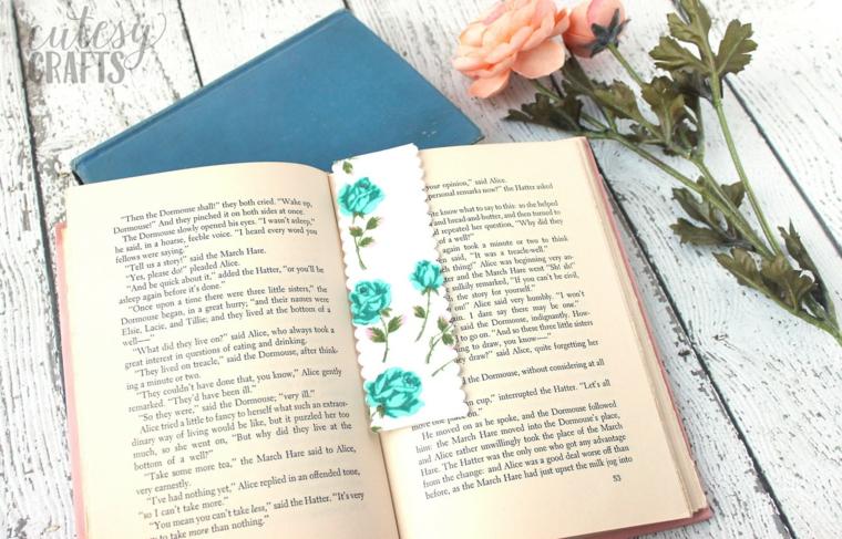 Libro aperto su un tavolo di legno, segnalibro forma rettangolare con disegno di rose
