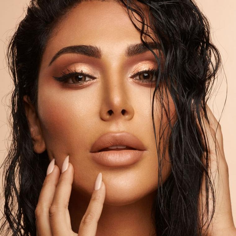 Huda Beauty con rossetto mat, ombretto marrone glitter, trucco occhi scuri