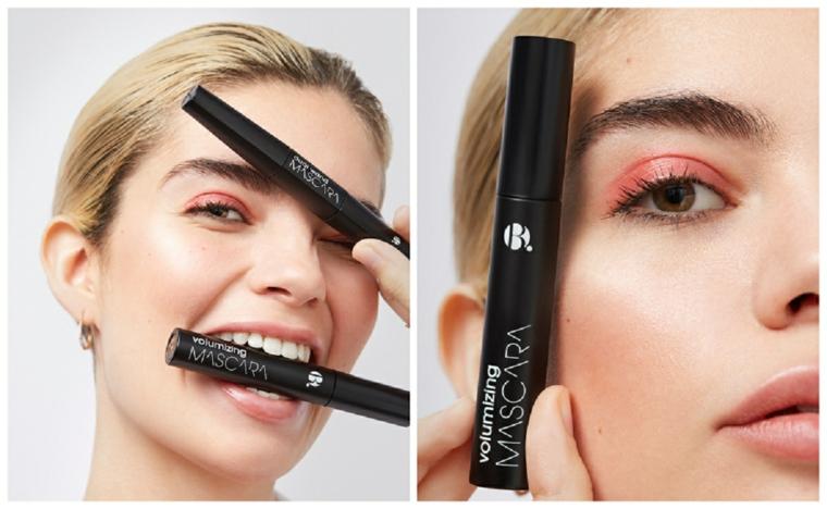 Make up occhi marroni, donna che tiene tra le dita un mascara di colore nero