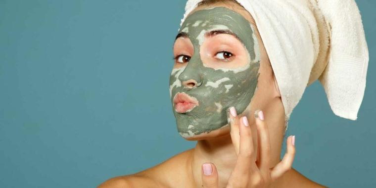 Donna che si mette una maschera all'argilla verde, donna con un'asciugamano sulla testa
