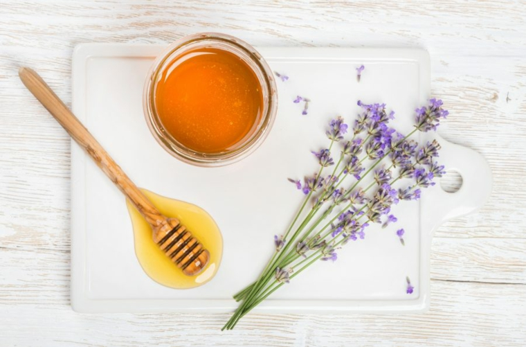 Ciotola di vetro con miele, fiori di lavanda su un tagliere di colore bianco