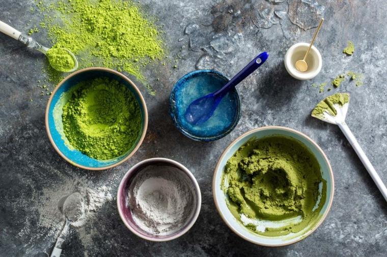 Ciotole con polvere di colore verde, ingredienti su un tavolo per maschera viso