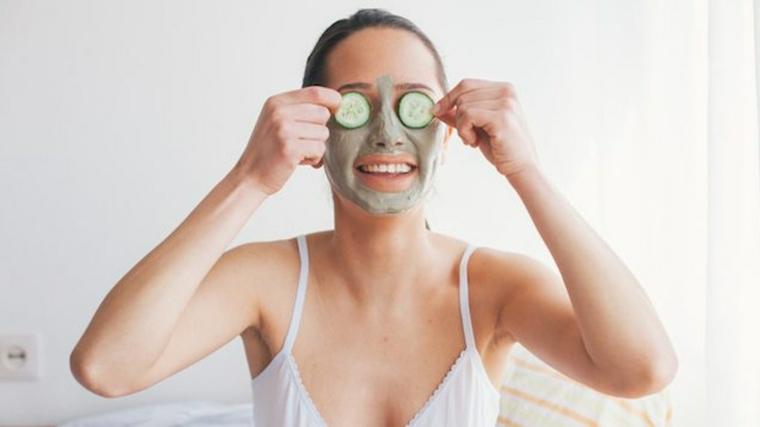 Donna con maschera sul viso, donna con cetrioli sugli occhi sorridente