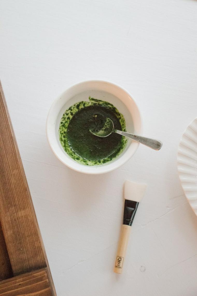 Ciotola con maschera al tè verde matcha, pennello su un tavolo di colore bianco