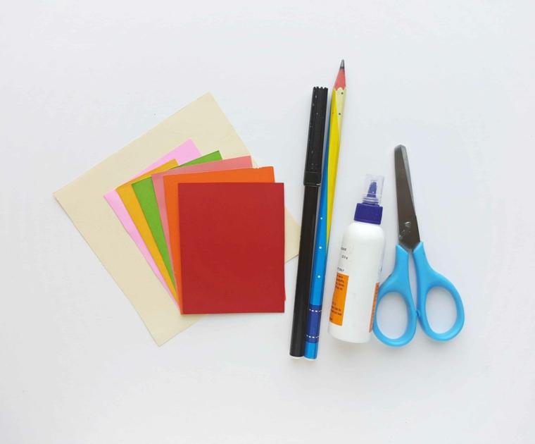 Cartoncini quadrati colorati accanto ad un pennarello nero, segnalibri per bambini