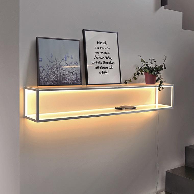 Mensola di metallo con quadri e pianta. illuminazione con fili luminosi