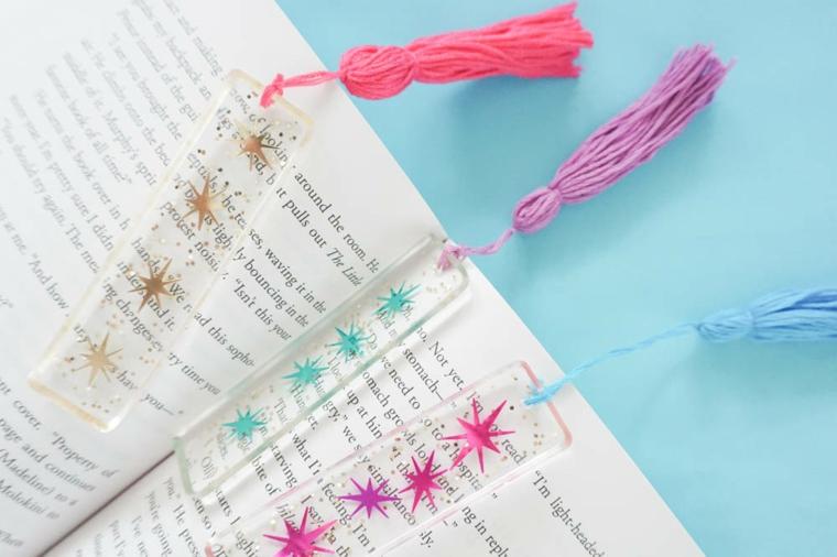 Segnalibri di plastica con disegni e nappe di filo di lana, libro aperto con segnalibro