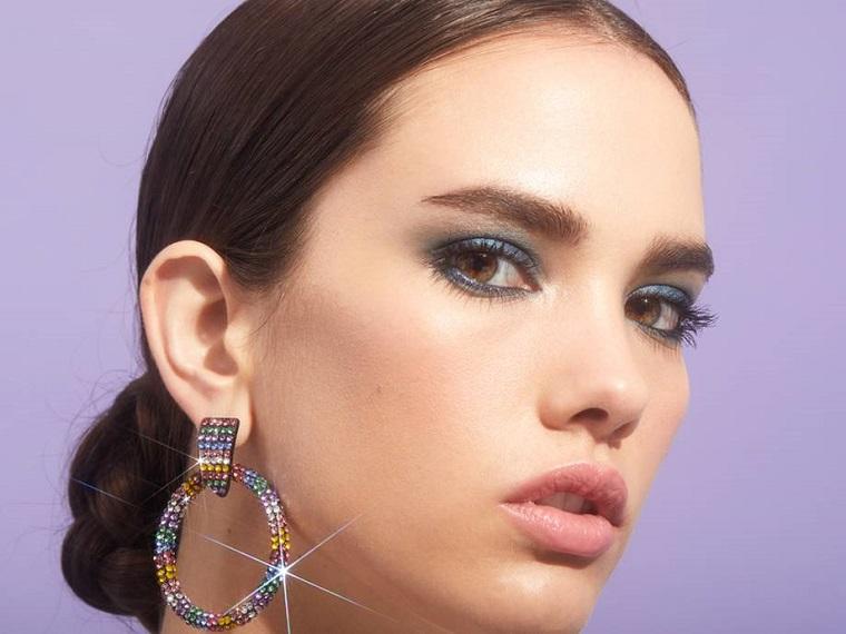 Trucco per occhi con ombretto di colore blu, trucco occhi marroni, orecchini rotondi con brillantini