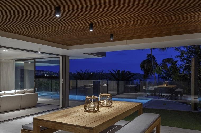 Soffitto in legno con faretti, open space con soggiorno e sala da pranzo