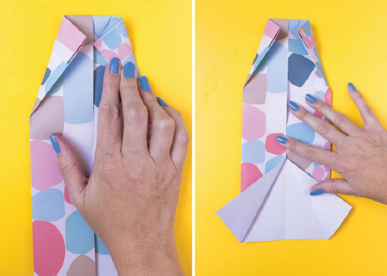 La mano di una donna che piega un foglio di carta colorato, biglietto auguri festa del papà