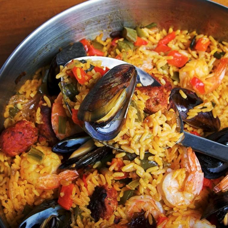 Padella con paella ai frutti di mare e salame, primi piatti sfiziosi, cucchiaio con riso e cozza