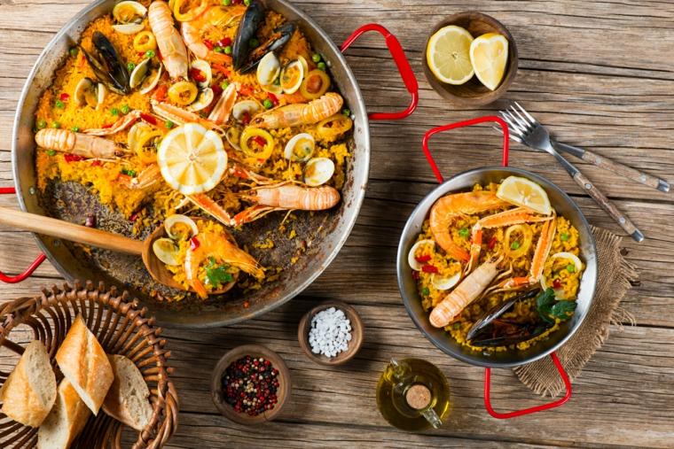 Primi piatti sfiziosi, padella con paella ai frutti di mare, cestino con pezzi di pane