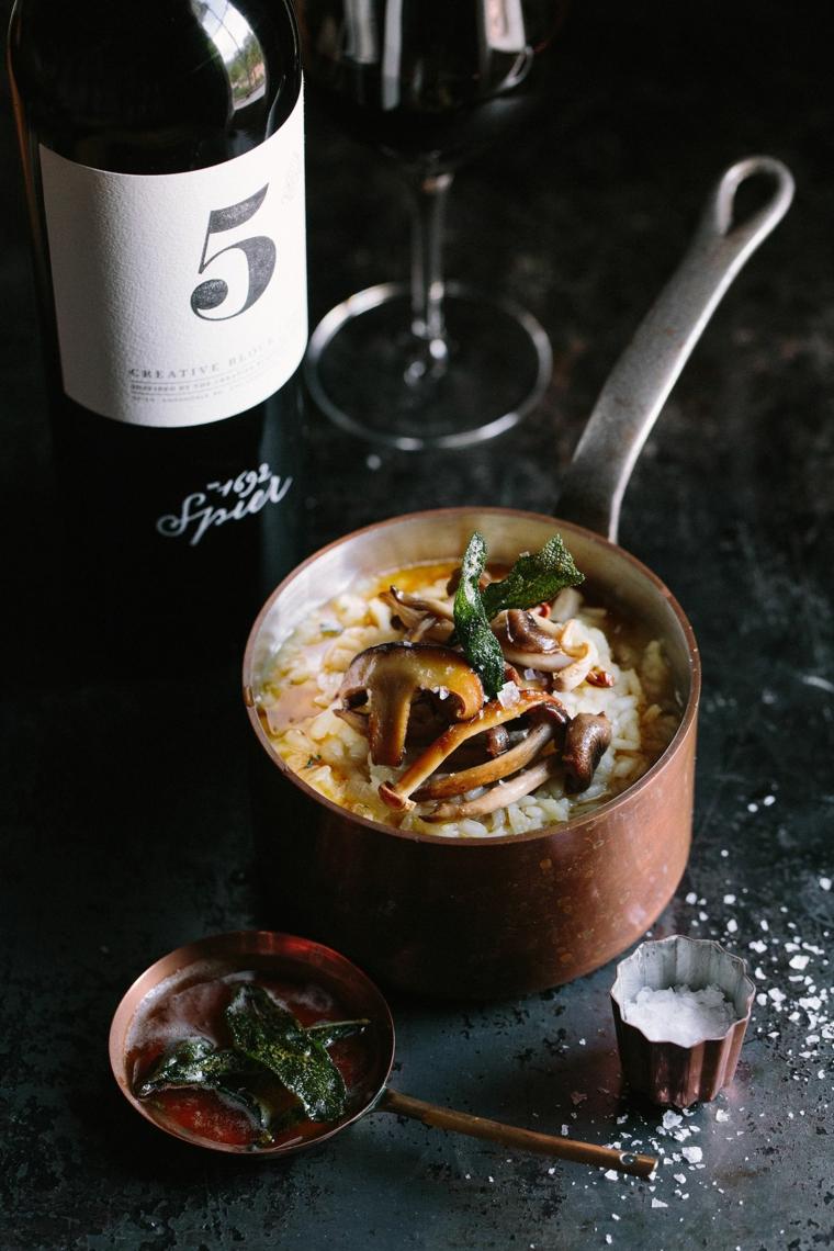 Casseruola con risotto ai funghi, bottiglia di vino rosso, primi piatti sfiziosi