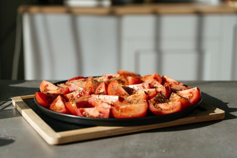 Teglia con pomodori a fette conditi con spezie, primi piatti estivi