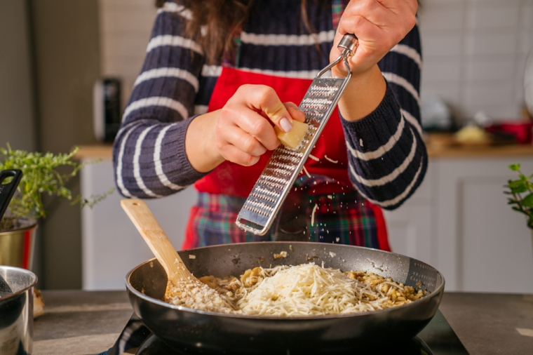 Primi piatti veloci ed economici, donna che grattugia il parmigiano in una padella