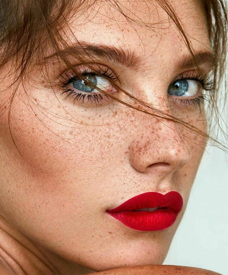 Ragazza con occhi blu e un leggero mascara, ragazza con lentiggini e rossetto rosso mat