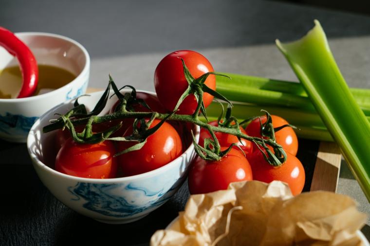 Primi piatti sfiziosi, ciotola con ramo di pomodori, gambo di sedano