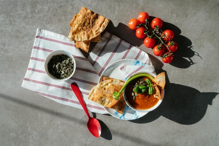 Ricette estive primi piatti, ciotola con zuppa di pomodoro, ramo di pomodori
