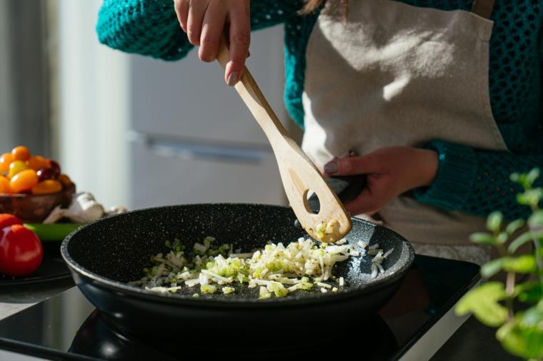 Donna che prepara un soffritto di sedano e cipolla, ricette estive veloci ed economiche