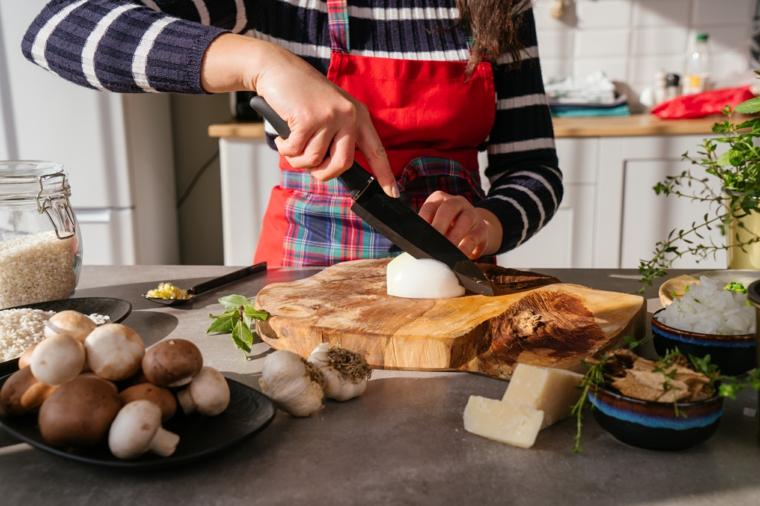 Donna che taglia la cipolla su un tagliere di legno, primi piatti sfiziosi