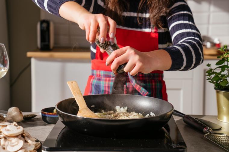 Donna che prepara un soffritto in padella, ricette primi piatti veloci