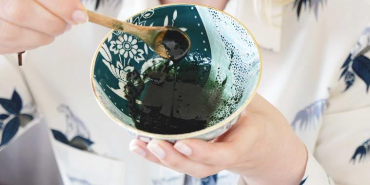 Donna che tiene una ciotola, ciotola con impasto di colore verde e cucchiaio di legno