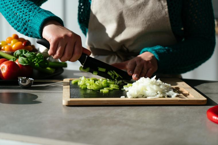 Donna che taglia il sedano su un tagliere di legno, primi piatti sfiziosi