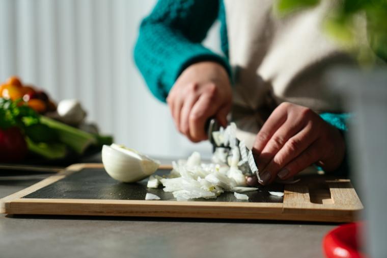Donna che taglia una cipolla su un tagliere, cena veloce e appetitosa