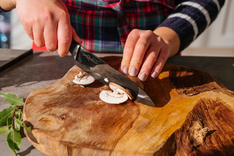Primi piatti estivi, donna che taglia i funghi su un tagliere di legno