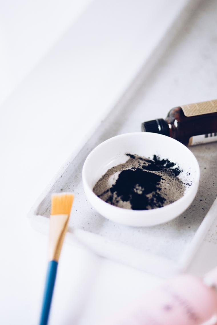 Maschera viso idratante fai da te, ciotola con polvere di argilla e gocce di olio essenziale
