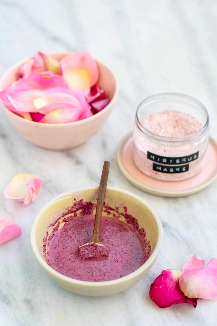 Ciotola con impasto di petali di rosa e acqua, barattolo con crema di colore rosa