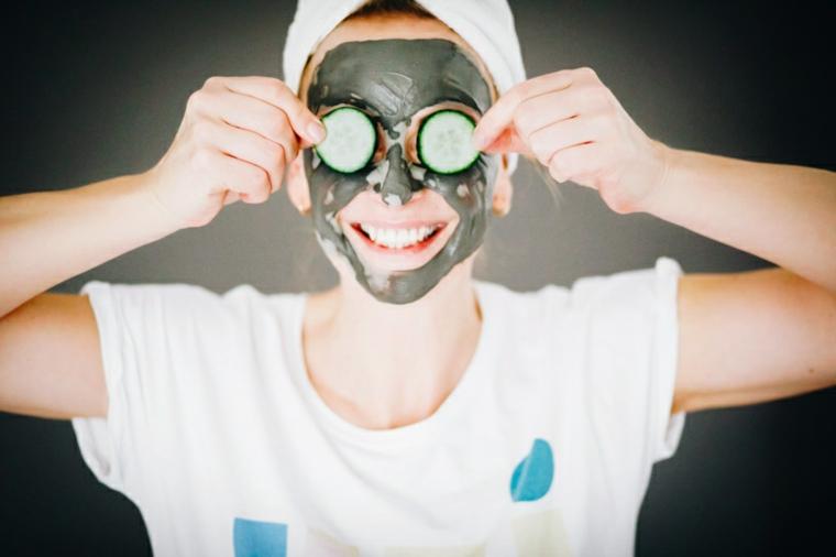 Donna con una maschera di argilla sul viso, donna con cetrioli sul viso, maschera per brufoli