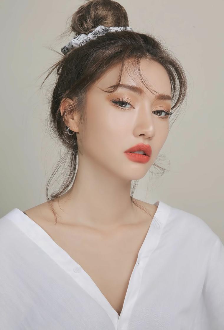 Ragazza con camicia bianca con bottoni, rossetto colore pesca e ombretto, make up donna