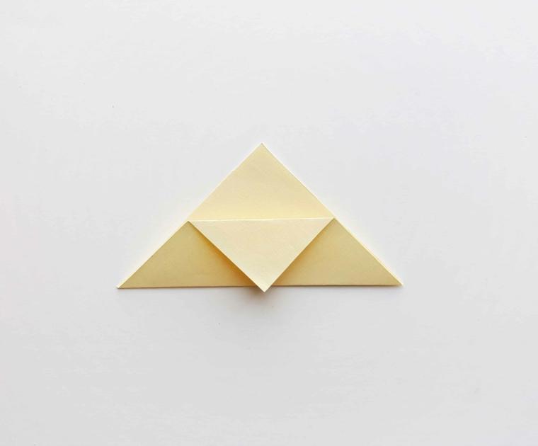 Origami con un foglio di colore bianco crema, creare segnalibri design unicorno